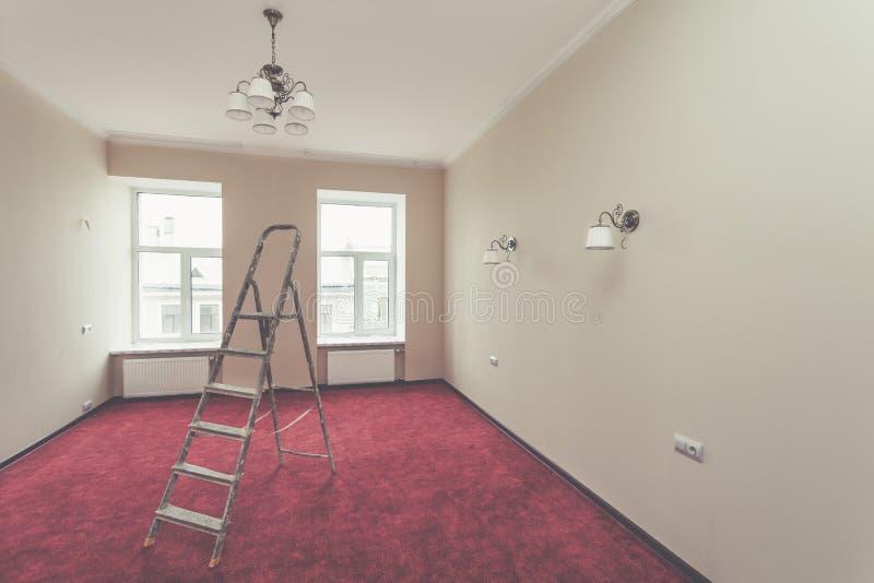 Binnenland van verbeteringsflat met ladder en sommige badkamersinrichtingen na het remodelleren, vernieuwing, uitbreiding, restau stock afbeeldingen