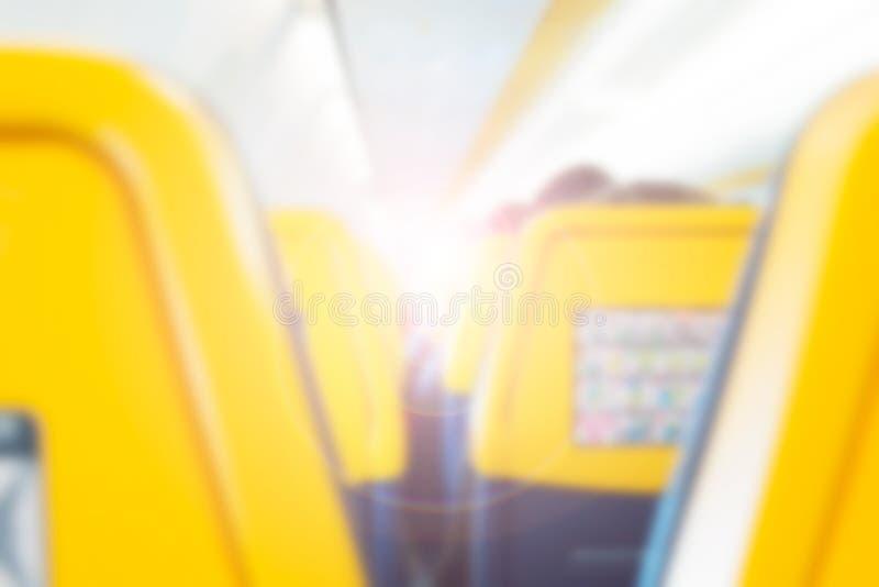 Binnenland van vliegtuig met passagiers die op zetels als onscherpe achtergrond zitten Reisconcept, toon met zonlicht royalty-vrije stock foto's