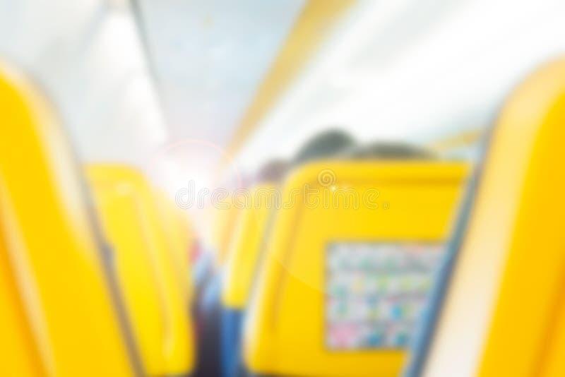 Binnenland van vliegtuig met passagiers die op zetels als onscherpe achtergrond zitten Reisconcept, toon met zonlicht royalty-vrije stock foto