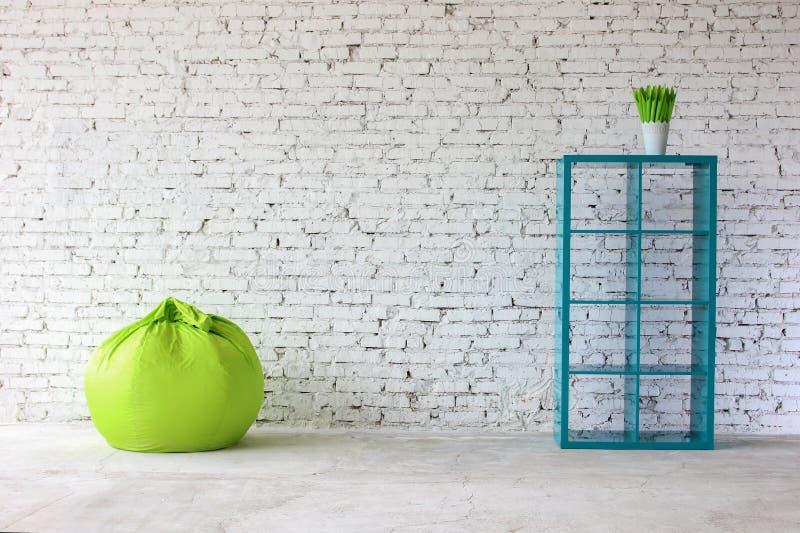Binnenland in witte baksteen met een boekenrek stock afbeelding