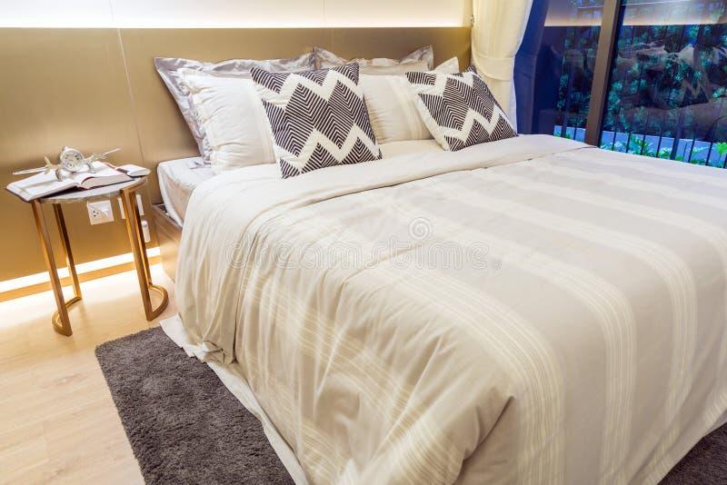 Binnenlands beeld van slaapkamer met beige en gouden kleur stock fotografie