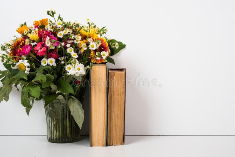 Binnenlands huisdecor met bloemen en boeken, eenvoudige de zomerdecoratie stock foto's