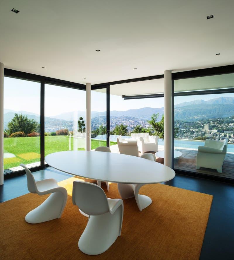 Binnenlands modern huis, eetkamer stock afbeelding