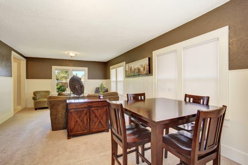 Binnenlands ontwerp Bruine houten die lijst in de eetkamer met beige tapijt wordt geplaatst stock afbeelding