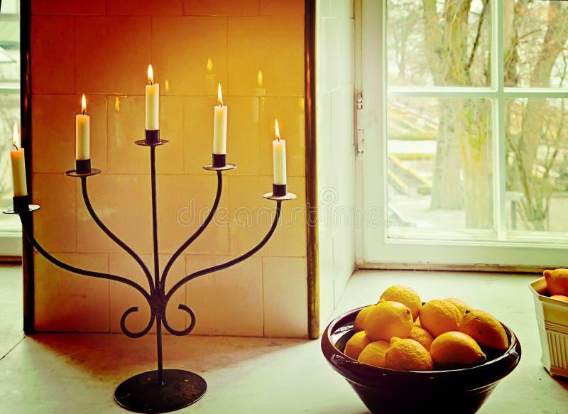 Binnenlands stilleven, kaarshouder met aangestoken kaarsen en oranje B stock foto's