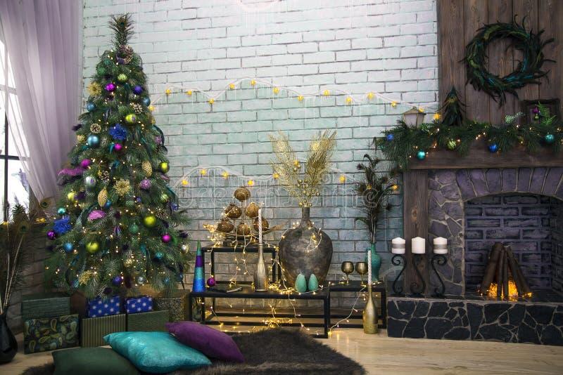 Binnenlandse die ruimte in Kerstmisstijl wordt verfraaid De Kerstmisboom door lichten wordt verfraaid, stelt, pauwveren, giften,  royalty-vrije stock foto