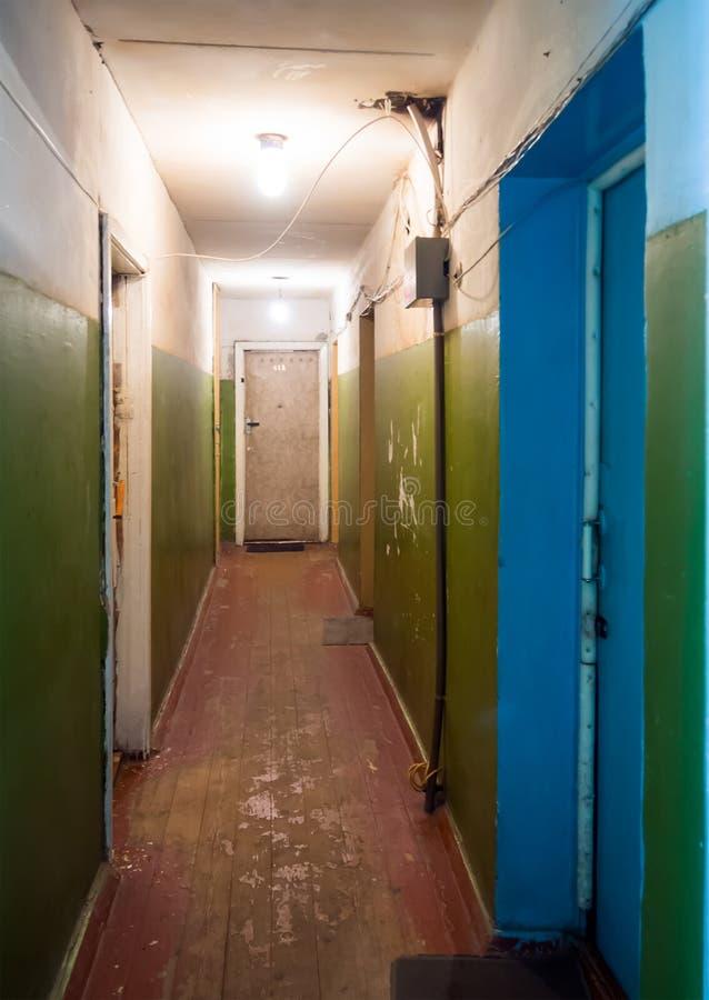 Binnenlandse gang dilapidated deur van de flat in een oude slaapzaal royalty-vrije stock afbeeldingen
