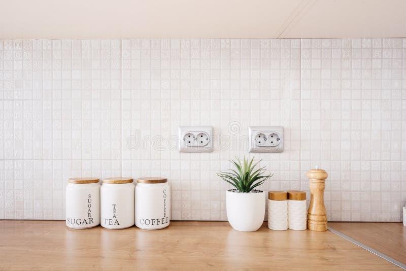 Binnenlandse kabinetten in moderne keuken, Eigentijds houten meubilair met suiker, thee en koffiekommen stock afbeeldingen