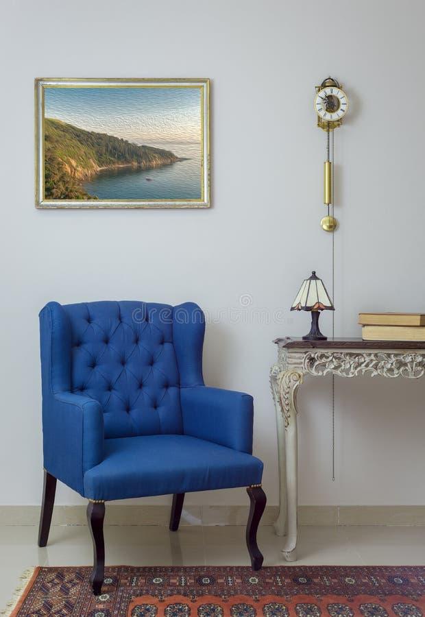 Binnenlandse samenstelling van retro blauwe leunstoel, uitstekende houten beige lijst, schemerlamp, boeken, en slingerklok over v stock afbeeldingen