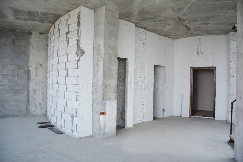 Binnenlandse zaalruimte in aanbouw, de lateibalken van de metaaldeur Muur zonder plasterwork en klaar te remodelleren stock afbeelding