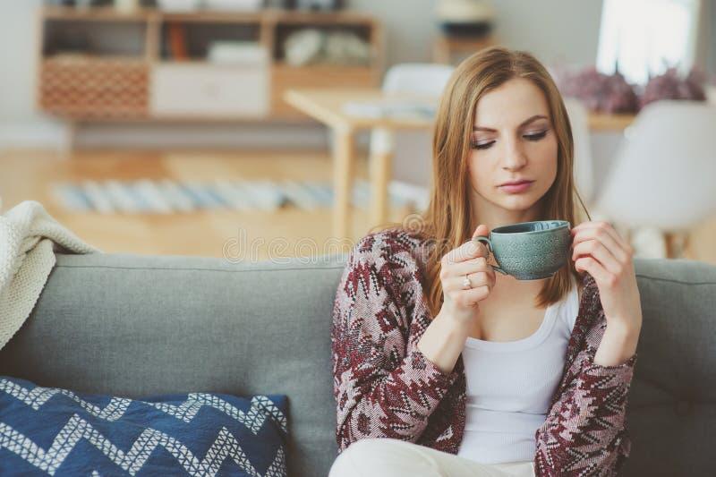 binnenlevensstijlportret van het jonge vrouw ontspannen thuis met kop van hete thee of koffie royalty-vrije stock afbeelding
