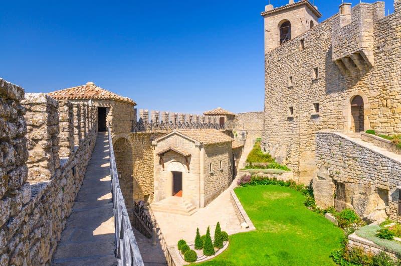 Binnenplaats met groen grasgazon van de eerste middeleeuwse toren van Prima Torre Guaita met de vestingsmuur van de steenbaksteen stock foto's