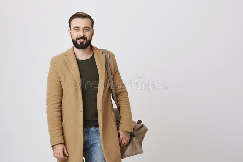 Binnenportret die van aantrekkelijke zakenman in laag en vrijetijdskleding, zak op schouder houden en bij camera glimlachen stock foto