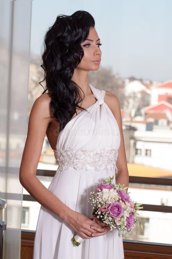 Binnenportret van aanbiddelijke bruid met zwart lang haar voor venster stock afbeeldingen