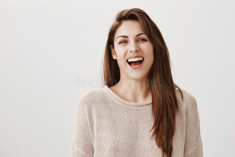Binnenportret van aantrekkelijke gewone Europese vrouw met het lange bruine haar luid lachen uit terwijl het staren bij camera royalty-vrije stock foto's