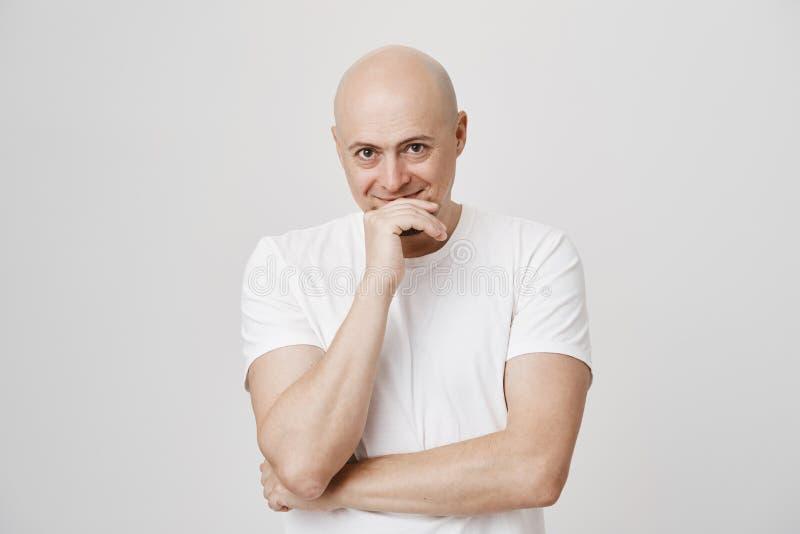 Binnenportret van de aantrekkelijke enige kale Europese mens die terwijl het behandelen van mond met hand, die van onder brows ki stock foto