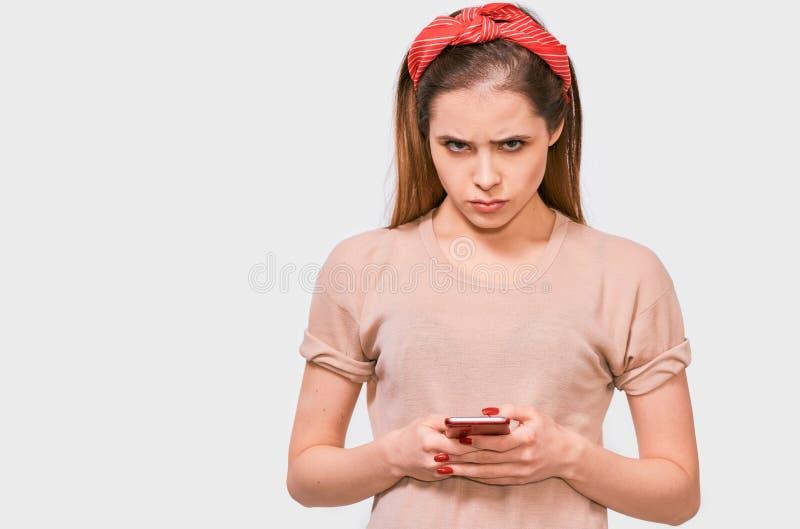 Binnenportret van droevige jonge atrractive vrouwelijke holdings mobiele telefoon in haar handen die bericht van haar vriend leze royalty-vrije stock afbeeldingen