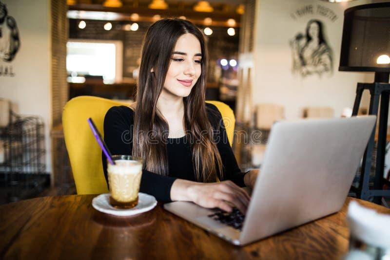 Binnenportret van een jong meisje dat zij aangezien een freelancer in een koffie die drinken een heerlijke hete Kop van koffie va royalty-vrije stock fotografie