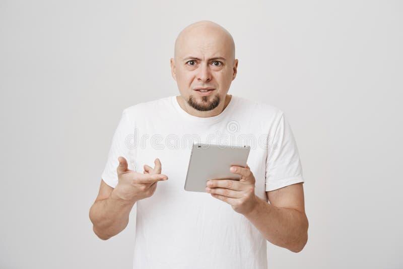 Binnenportret van geïrriteerde verstoorde kale Kaukasische mannelijke holding tablet en het richten op het, terwijl het fronsen e royalty-vrije stock afbeeldingen