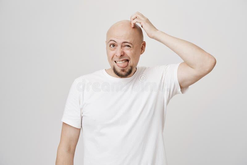 Binnenportret van grappig kaal Kaukasisch mannelijk krassend hoofd terwijl uit omhoog, fronsende en plakkende het kijken tong stock fotografie