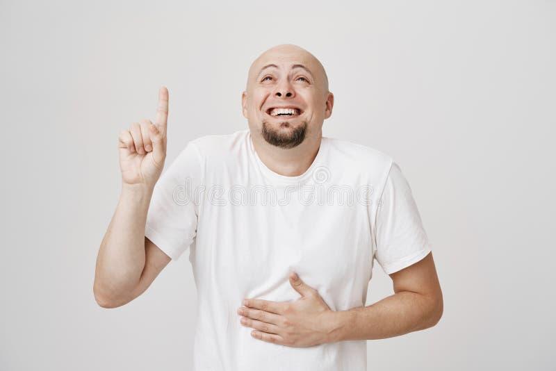 Binnenportret van het charmeren van de grappige Europese kale mens met baard die omhoog op met wijsvinger wijzen terwijl het lach royalty-vrije stock afbeeldingen