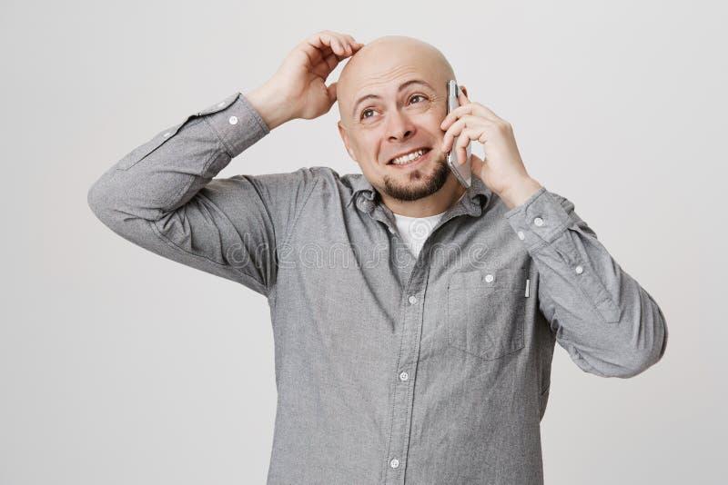 Binnenportret van leuk kaal Kaukasisch mannelijk krassend hoofd terwijl het spreken op smartphone, die terwijl omhooggaand het ki stock fotografie