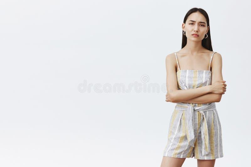 Binnenschot die van humeurig en bazig knap Aziatisch vrouwelijk model met schone huid en lang donker haar, handen gekruist houden stock afbeelding