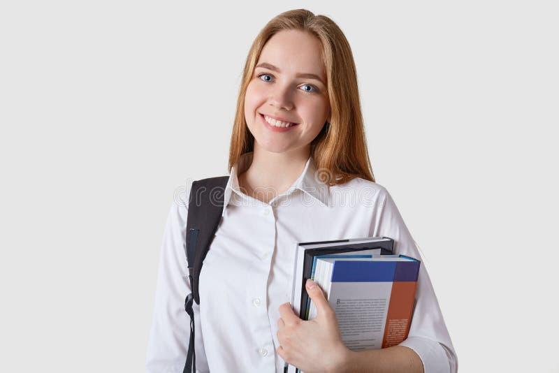 Binnenschot die van mooi tienermeisje met zwarte rugzak en document omslag in handen, gelukkige, aantrekkelijke studentenvrouw ki stock foto's