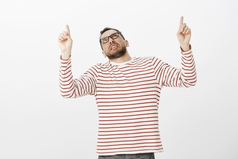 Binnenschot die van ontstemde weerzinwekkende volwassen kerel in buitensporige gestreepte trui, en met antipathie benadrukken kij royalty-vrije stock afbeeldingen