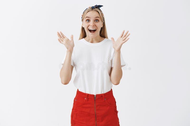 Binnenschot die van tevreden gelukkig aantrekkelijk Kaukasisch meisje die met eerlijk haar palmen in vreugde opheffen, ruim gliml royalty-vrije stock afbeelding