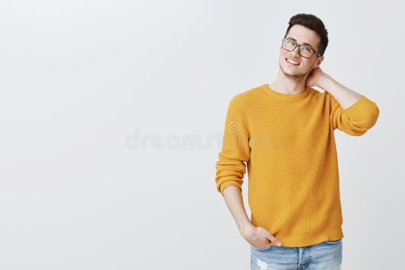 Binnenschot van charmante aardige en knappe jonge kerel in glazen en gele sweater wat betreft rug van halsgooi en onzeker stock afbeeldingen