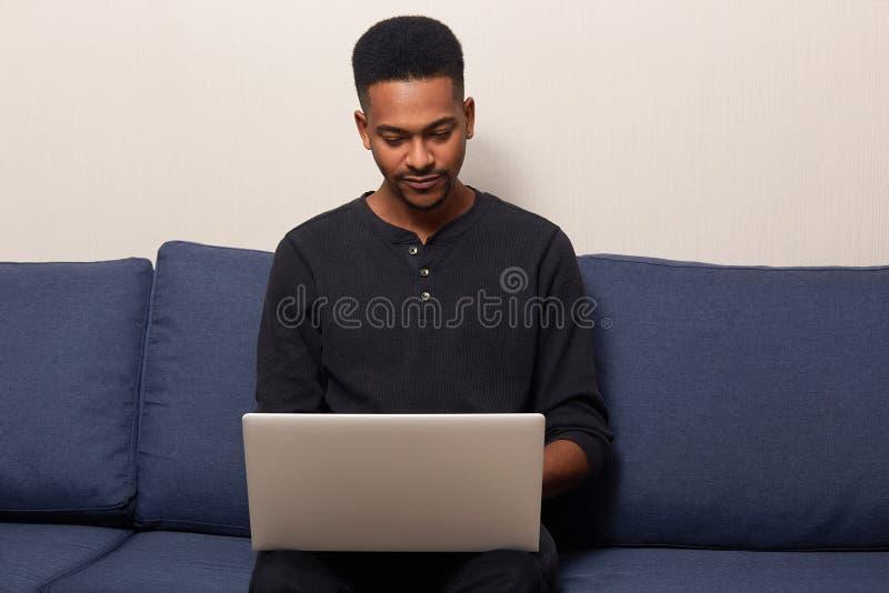 Binnenschot van donker gevild jong mannetje die thuis online, surfend Internet aan draagbare laptop computer werken, die zitten royalty-vrije stock foto