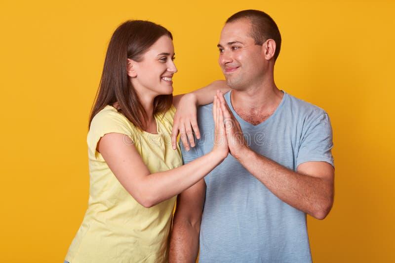 Binnenschot van gelukkige kerel en het vrolijke Kaukasische dame raken met palmen tegen gele achtergrond, paar in liefde die zich stock afbeelding