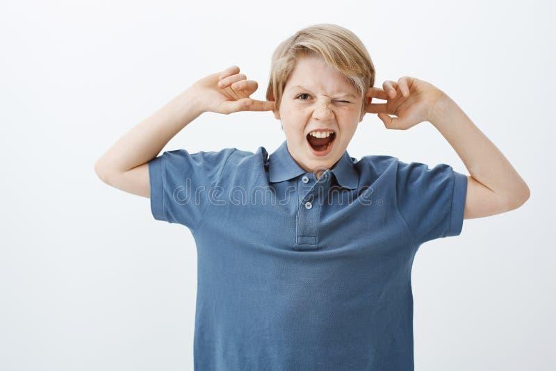 Binnenschot van ongelukkig geërgerd jong Europees kind in blauwe t-shirt, schreeuwen of schreeuwen, die oren behandelen met index stock afbeelding