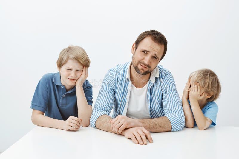 Binnenschot van ontstemde jonge zonen en vaderzitting bij lijst, jammerend en wordt verstoord, fronsend van afkeer stock fotografie