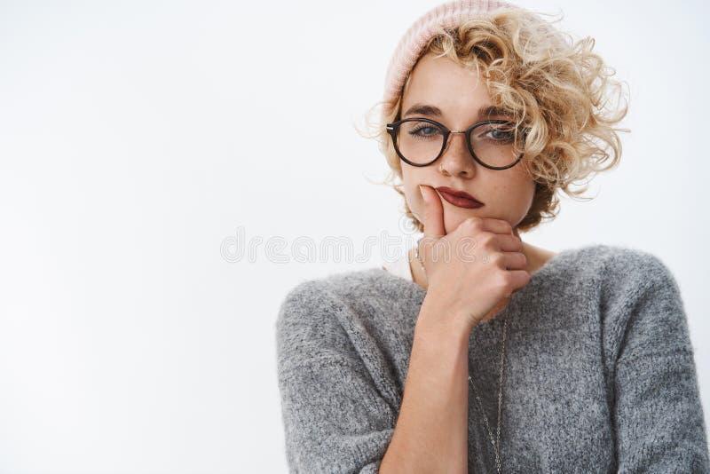Binnenschot van pietluttige en nadenkende creatieve vrouwelijke ontwerper die omhoog nieuwe ideeën maken die warme beanie en de w stock afbeelding