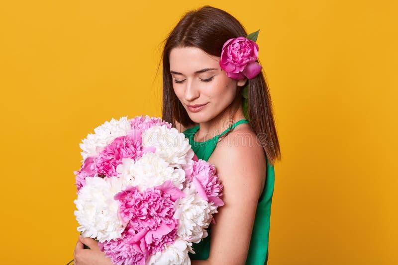 Binnenschot van zoete aanbiddelijke jonge dame die van boeket van bloemen, tevreden met de lenteheden genieten, die geur van pioe royalty-vrije stock foto