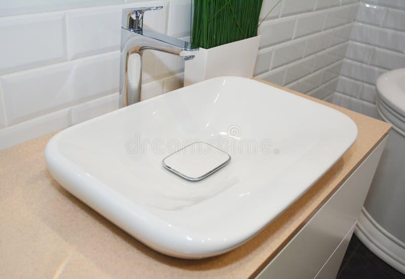 Binnenshuis van de badkamer met betegelde muren en witte keramische gootsteen stock afbeelding