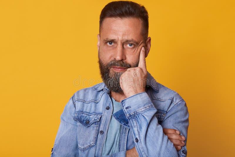 Binnenstudioschot van het ernstige magnetische blauwe eyed mens stellen geïsoleerd over heldere gele achtergrond, die toevallig j stock foto