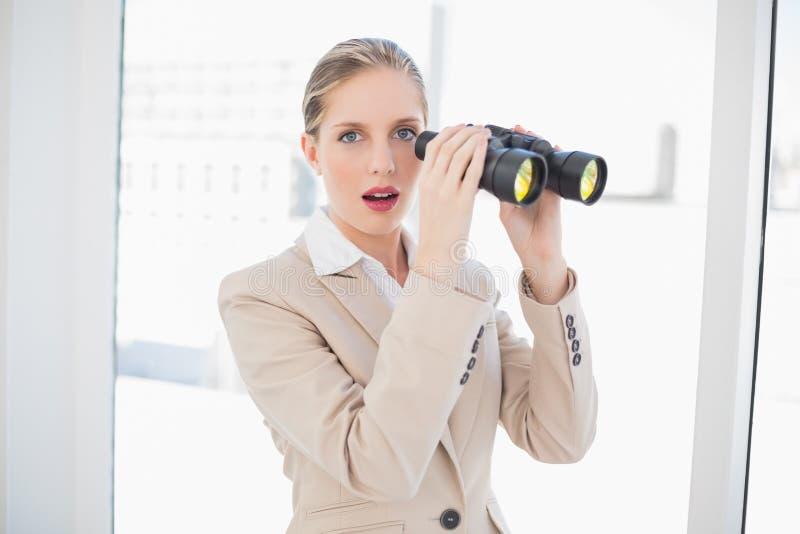 Binocolo biondo colpito della tenuta della donna di affari fotografia stock