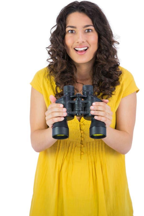 Binocolo casuale sorridente della tenuta della giovane donna immagini stock