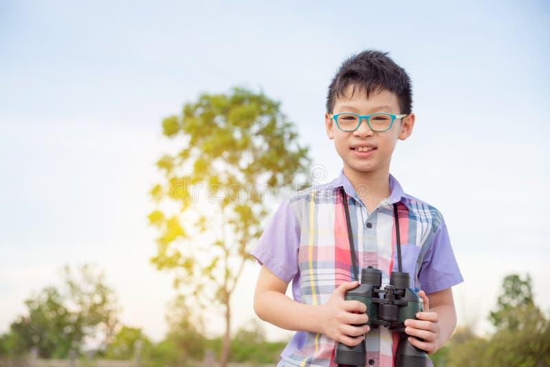 Binocolo della tenuta del ragazzo in foresta immagini stock libere da diritti