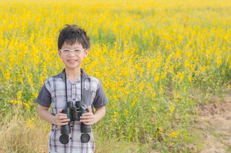 Binocolo della tenuta del ragazzo nel giacimento di fiore immagini stock
