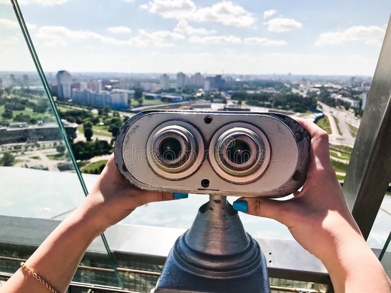 Binocolo fisso d'esame contro il binocolo grigio sulla piattaforma di osservazione ad altezza nelle mani di una ragazza con il ch fotografia stock