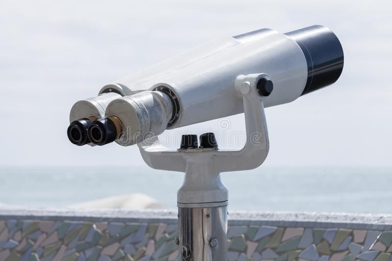 Binocular telescope outdoor photo. Binocular telescope on a rotating base mounted on an outdoor touristic viewpoint stock image