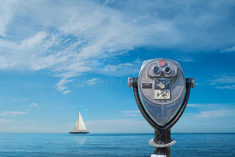 Binocular viewer overlooking sea. With sailing boat on horizon against blue sky royalty free stock photos