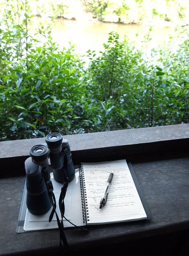 Binoculars and bird watching notes stock image