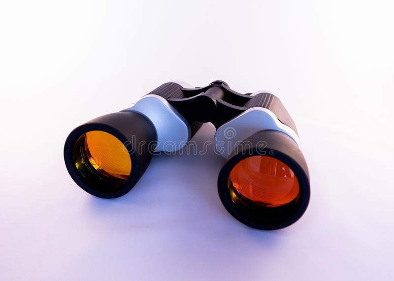 Binoculars with colored orange lenses on a white background royalty free stock photography