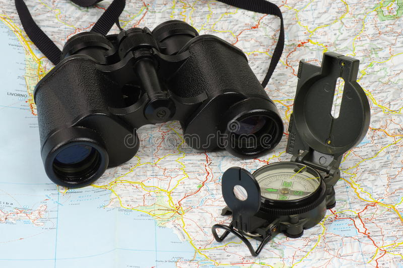 Binoculars, compass and map. Porro binoculars and military compass lying on the map royalty free stock photography