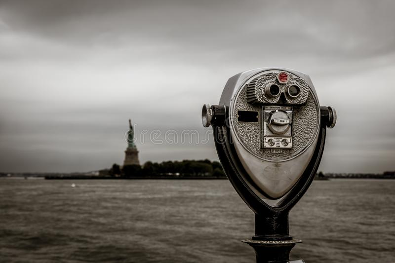 Binoculars in Ellis Island with view to the liberty statue new york stock images